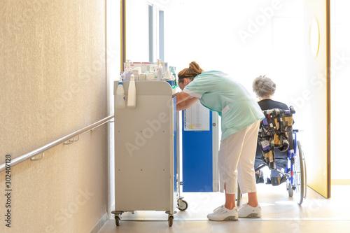 Aide soignante au travail accompagne personne agée en fauteuil roulant dans coul Canvas Print