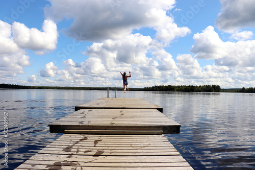 Girl jumping off the end of a pier at a lake in Finland