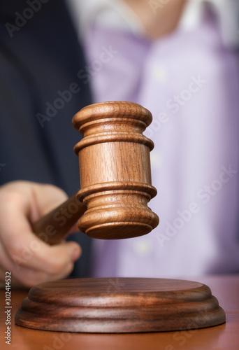 wooden gavel in hand - 302414532