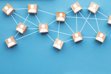 Wooden blocks connected together on a blue background. Teamwork concept