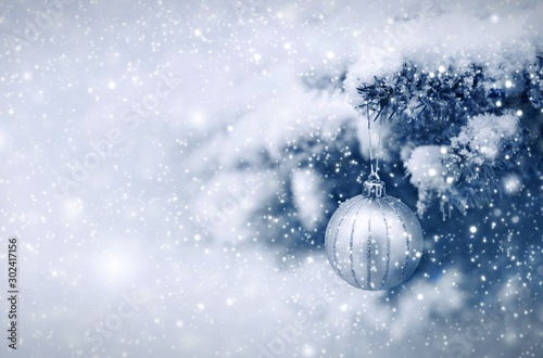Obraz Silver Christmas Ball hanging on a Fir Tree Branch. Christmas Background. - fototapety do salonu