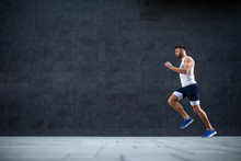 Side View Of Handsome Caucasian Muscular Fit Man Running Fast Outdoors. In Background Is Gray Wall.