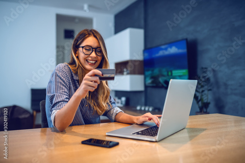 Fototapeta Young attractive smiling Caucasian woman with eyeglasses holding credit card and typing number of her bank account on laptop while sitting at dining table. Online shopping concept. obraz