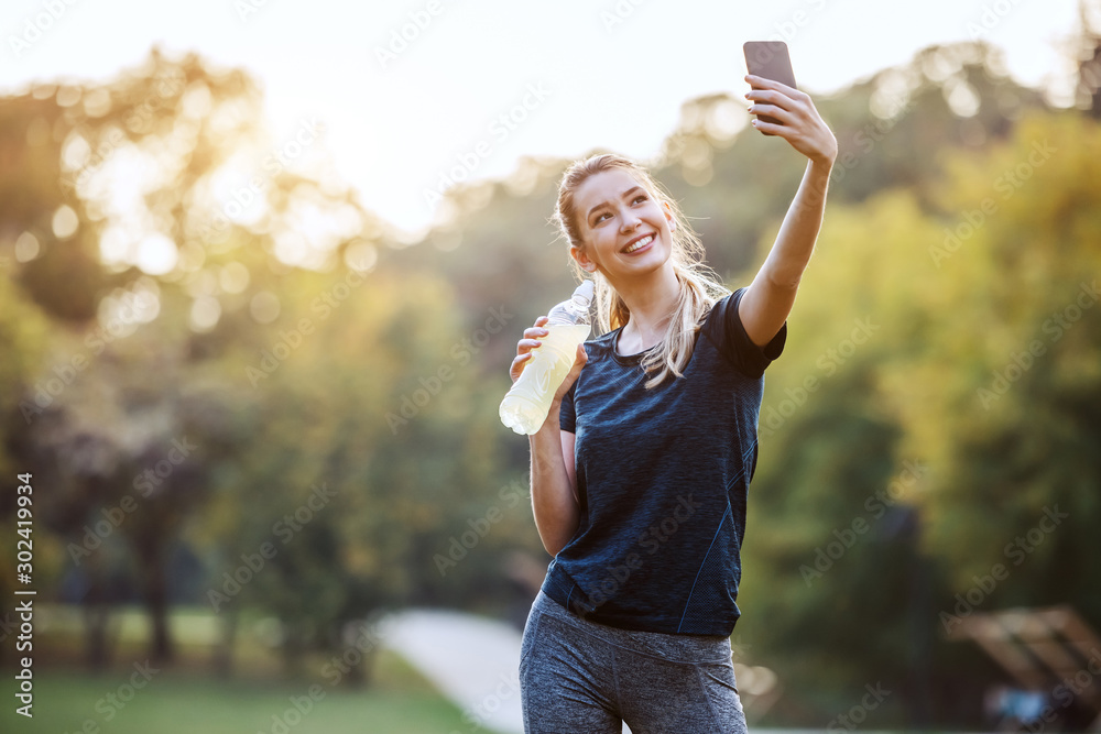 Fototapety, obrazy: Beautiful caucasian sportswoman in sportswear and with ponytail standing in nature, holding bottle with refreshment and taking selfie. Fitness in nature concept.