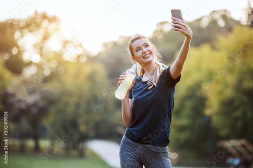 fototapeta na drzwi i meble Beautiful caucasian sportswoman in sportswear and with ponytail standing in nature, holding bottle with refreshment and taking selfie. Fitness in nature concept.