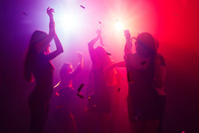 Celebrating. A Crowd Of People In Silhouette Raises Their Hands On Dancefloor On Neon Light Background. Night Life, Club, Music, Dance, Motion, Youth. Purple-pink Colors And Moving Girls And Boys.