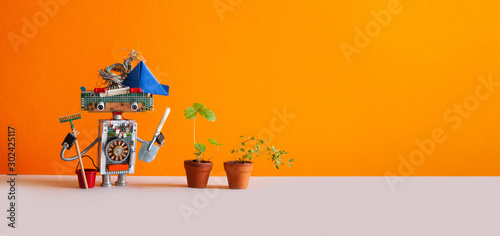 Obraz Agriculture gardening poster. Toy gardener with bucket shovel rake and sprouts of wild strawberries in clay flower pots. Orange background, copy space - fototapety do salonu