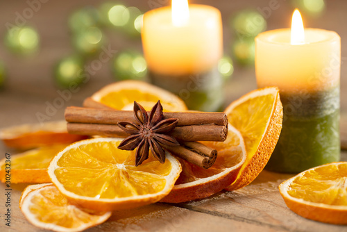 Photographie Christmas or advent decoration - candles with orange slices and spices on old wo