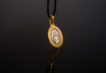 Gold Pendant On A Black Reflec...