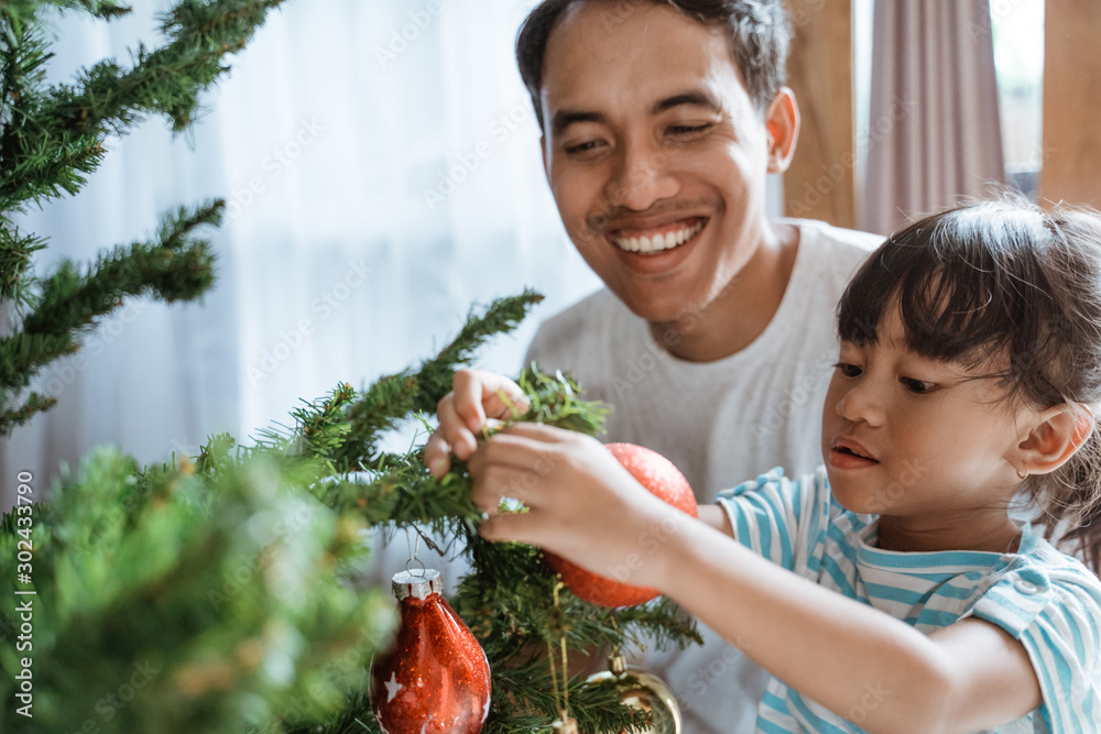 Fototapeta happy asian dad and girl decorating christmas tree together