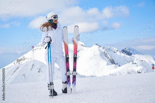 plakat woman skier wearing white healmet with mask in snow winter mountain