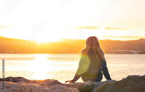 Obraz lonely girl sitting back to camera on stone sea bay waterfront shore line and enjoy by beautiful bright orange sunset light with colorful glares , thinking and human emotion concept photography  - fototapety do salonu