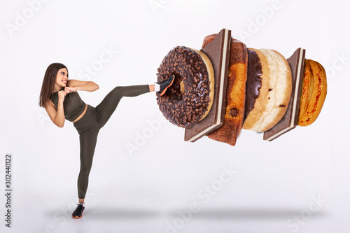 Fotografía Fit young woman fighting off sweets and candy, Fit young woman saying NO to unhe