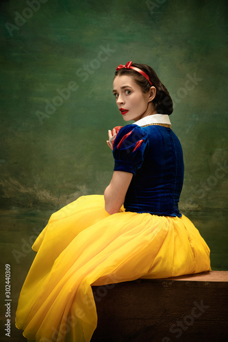 Young ballet dancer as a Snow White with poisoned apple in forest. Flexible caucasian ballerina dances like character of fairytail in bright clothes. Adorable and modern story in emotions.