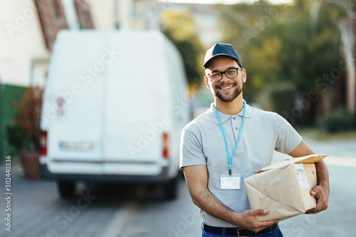 Fotografiet Portrait of young happy courier with packages for a delivery.