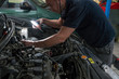 Auto mechanic working on car engine in mechanics garage. Car repair service.