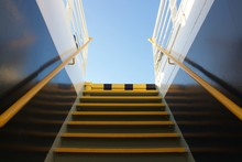 Looking At Clear Blue Sky At The Background Through The Narrow Metallic Staircase At The Exterior Of A Cruise Ship At Summer Holidays