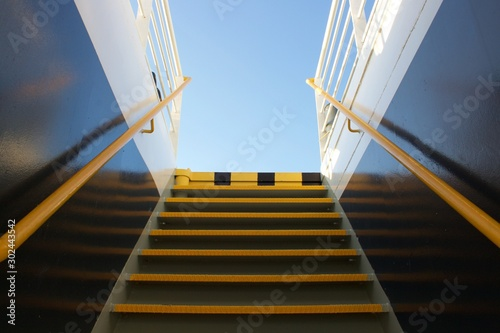 Looking at clear blue sky at the background through the narrow metallic staircas Fotobehang