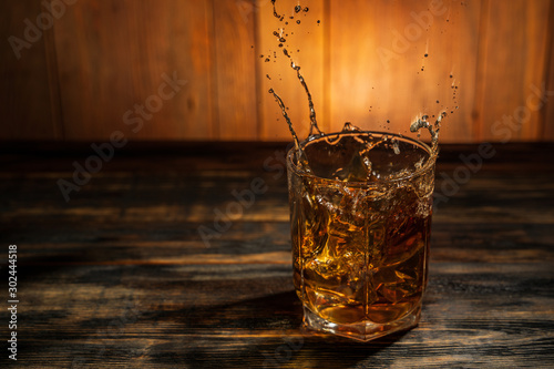 Foto auf Leinwand Alkohol glass of whiskey with spray on a wooden table in a bar