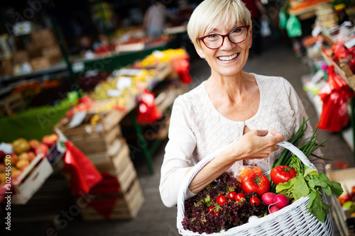Valokuva  Mature woman buying vegetables at farmers market