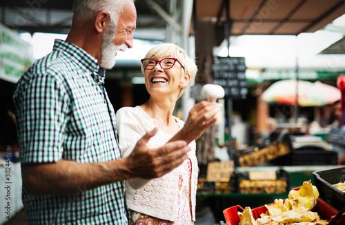 Obraz na plátně  Portrait of beautiful elderly couple in market buing food