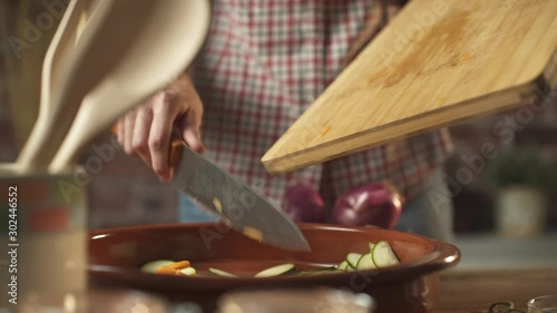 Fotografie, Obraz Woman pouring chopped vegetables in a pot