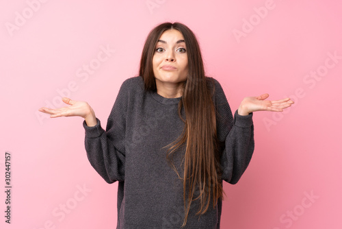 Fotografía  Young woman over isolated pink background having doubts while raising hands