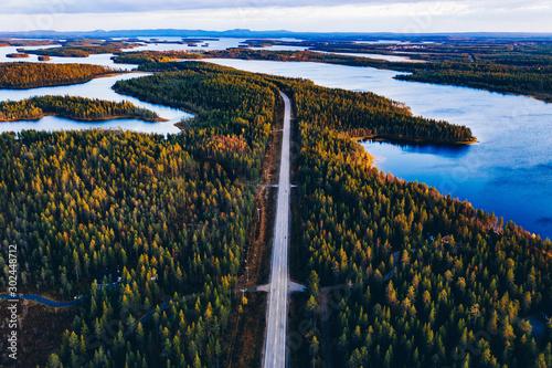 Autocollant pour porte Route dans la forêt Aerial view of road through autumn forest with blue lakes in Finland.