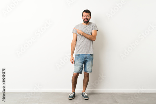 Fotomural  A full-length shot of handsome man with beard surprised and pointing side