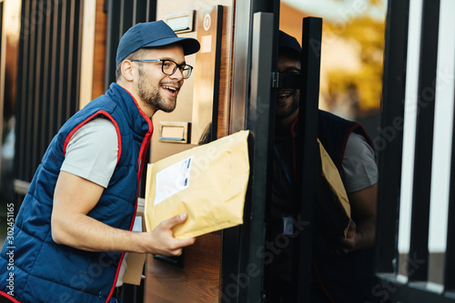 Fototapeta Happy courier communicating with customer over intercom while making home delivery