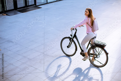 Obraz Young woman with modern city electric e-bike clean sustainable urban transportation - fototapety do salonu