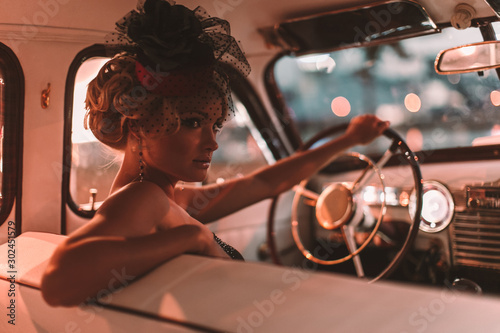 Obraz Portrait of beautiful sexy fashion blond girl. Model with bright makeup and curly hairstyle in retro style hat sitting in old car. Attractive woman  rides around the night city - fototapety do salonu