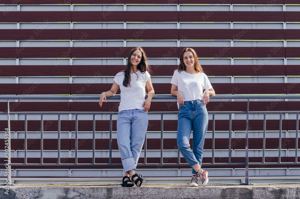 Fototapeta Two young hipster women leaning back on fence and making fun in front of urban wall