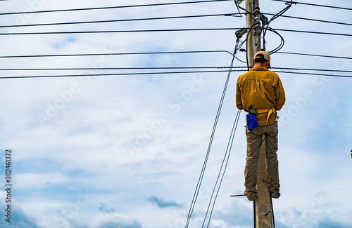 Fototapeta The technician is climbing on the electric pole for repairing electric problems in the background of cloudy blue sky, concept of risk for hazardous work