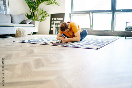 Healthy young man sitting in pose lotus on carpet and doing yoga exercises during morning workout in modern apartment.Hipster guy practicing meditation in stylish flat with home interior