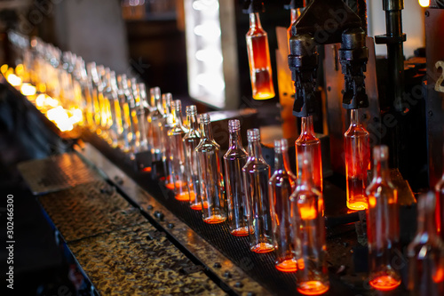 Photo Glassworks. Glass industry. The process of making glass bottles.
