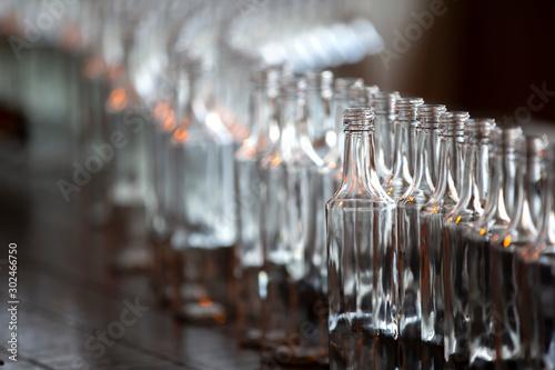 Foto auf Leinwand Alkohol Glassworks. Glass industry. Many glass bottles on a factory conveyor.