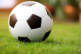 Fototapeta Sport - Close up soccer ball or football on green grass with sunrise background. Sport concept.