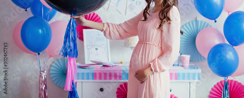 pregnant woman near pink and blue decorations at gender reveal party Wallpaper Mural
