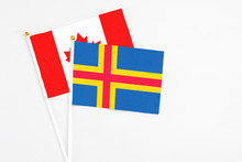 Aland Islands And Canada Stick Flags On White Background. High Quality Fabric, Miniature National Flag. Peaceful Global Concept.White Floor For Copy Space.