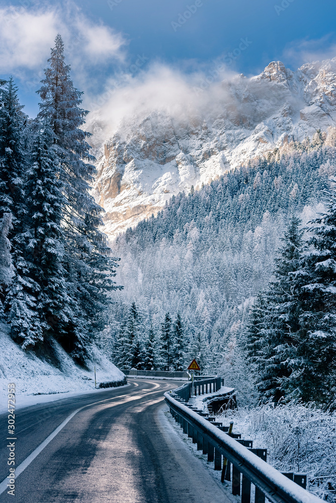 Fototapeta Curved road in the Italian Alps in South Tyrol, during winter / Sunny winter day with harsh shadows and lot of snow