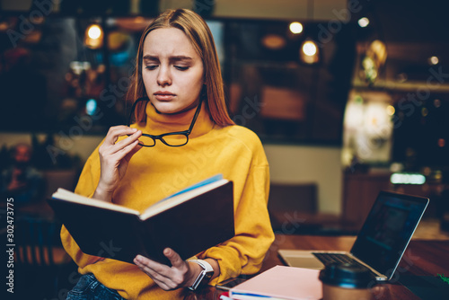 Vászonkép Charming talented sad female student wearing cool eyeglasses for better vision while preparing for upcoming examinations indoors