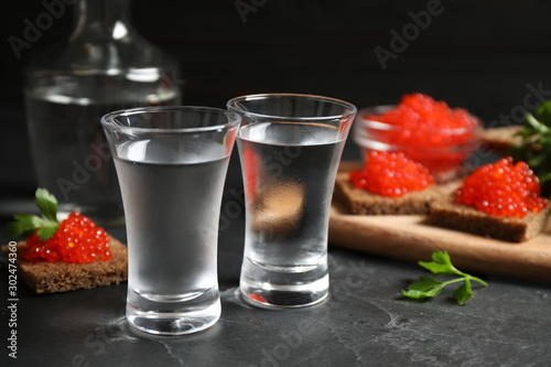 Cold Russian vodka and sandwiches with red caviar on black table, closeup Fototapeta