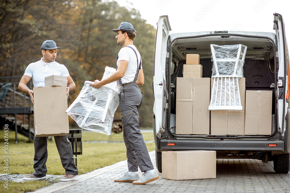 Fototapety, obrazy: Delivery company employees unloading cargo van vehicle, delivering some goods and furniture to a clients home. Relocation and professional delivery concept