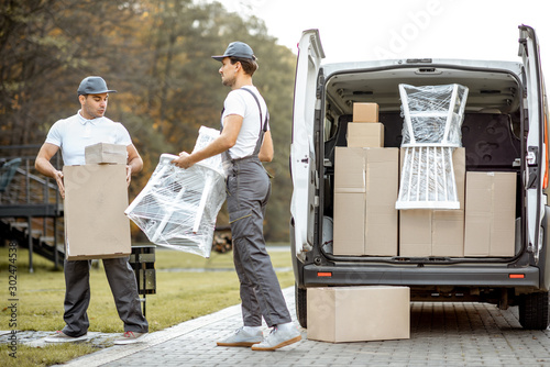 fototapeta na szkło Delivery company employees unloading cargo van vehicle, delivering some goods and furniture to a clients home. Relocation and professional delivery concept