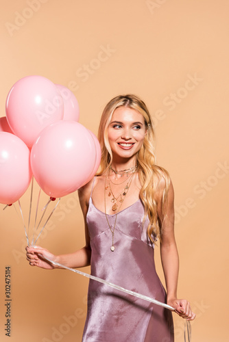 happy elegant blonde woman in violet satin dress and necklace holding pink balloons  on beige