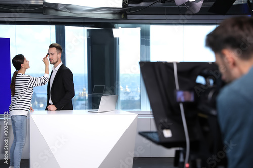 Fototapeta Presenter, makeup artist and video camera operator working in studio. News broadcasting obraz na płótnie