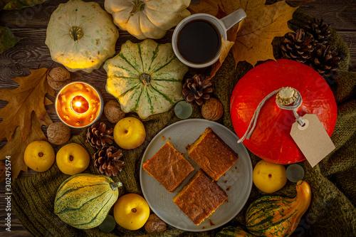 Cisto z dyni na jasnym talerzu, obok znajdują się dynie, pigwa, szyszki, liście, orzechy, kawa i świeczka