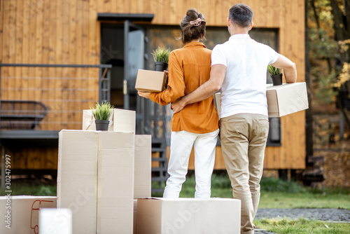 Young couple standing back with cardboard boxes in front of their new house Canvas