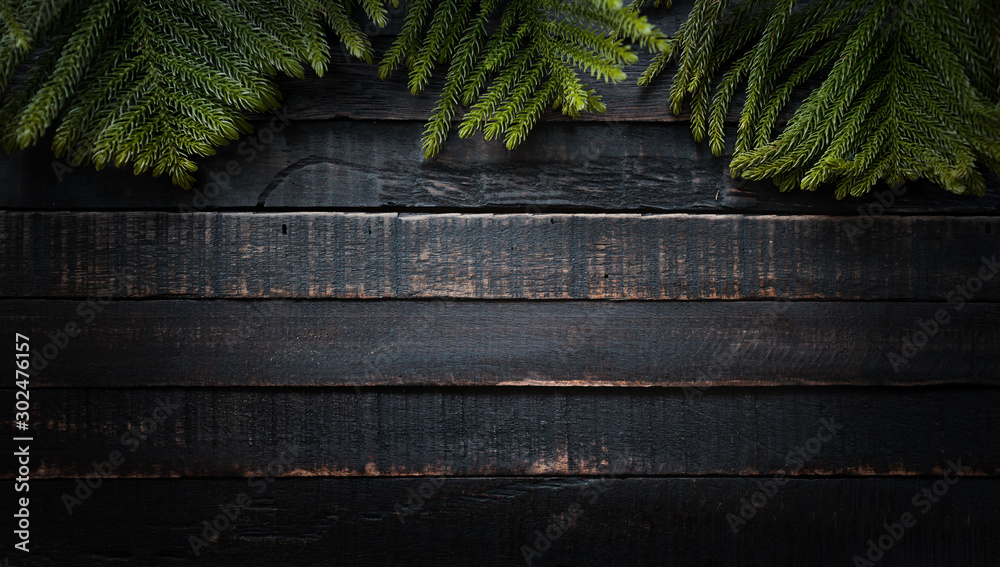 Fototapeta Christmas tree branches on dark wooden background  with copy space. Flat lay